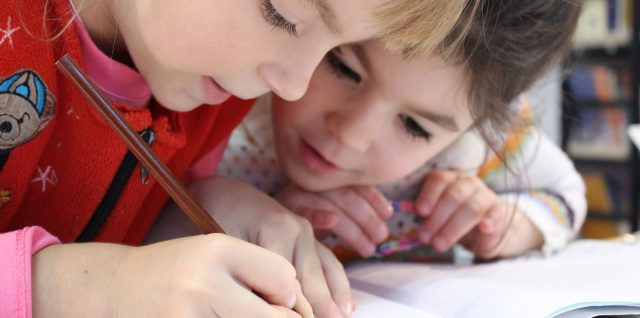 Image of two young children studying together