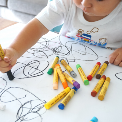 a photo of a young child drawing with crayons