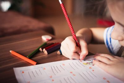 a photo of a child writing with a red pencil