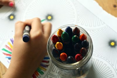 a photo of a cropped photo depicting a child's hand holding a crayon, drawing; a cup of crayons is next to the hand