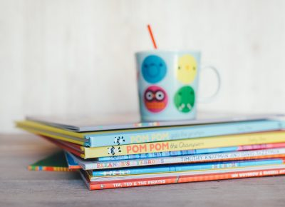 a photo of a stack of children's books with a fun mug on top of the stack